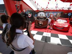 Getting your picture taken with Mater and Lightning McQueen is part of Disney's cross promotion of the Cars 2 movie as well as building interest in Cars Land, set to open in 2012.