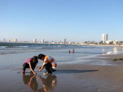 Teenagers pass the afternoon on a Mazatlan beach. The Mexican tourist town has seen a drop in visitors.