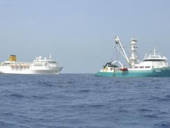 The Costa Allegra, left, is towed by French fishing vessel, The Trevignon, in the Indian Ocean, Tuesday.