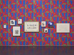 "Artwork is hung on wallpaper that plays on the famous Robert Indiana ""LOVE"" stamp using ""AIDS"" in green, blue and red. It is part of a new exhibit ""This Will Have Been: Art, Love and Politics in the 1980s"" at the Museum of Contemporary Art in Chicago"
