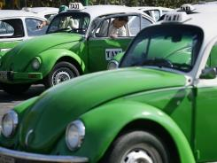 A man steps out of his Volkswagen beetle taxi during an inspection in Mexico City. Mexico City has announced that the last of the iconic Volkswagen Beetle taxis will be withdrawn from service by the end of 2012.