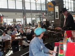 Grammy winner Ray Benson, with guitar, and pianist Rich Harney entertain travelers at the Austin-Bergstrom International Airport.