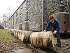 Traditional transport at distillery:  Darrell Berkley, of Taylorsville, Ky., rolls barrels on a track from the warehouse to the Woodford Reserve bourbon bottling facility in Versailles, Ky.