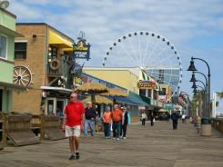 Visitors walk along the boardwalk in downtown Myrtle Beach, S.C. Driving NASCAR cars and flying along a zip line are among the new attractions for visitors to the resort town for the upcoming season.