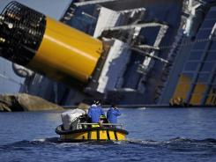 A small boat passes the stricken Costa Concordia on Jan. 26.