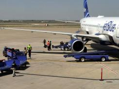 Officials search baggage from JetBlue Flight 191 on Tuesday at an airport in Amarillo, Texas. A pilot caused the flight to make an emergency landing.