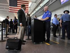 A TSA agent screens a traveler at Logan Airport in Boston.