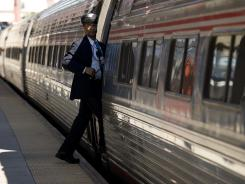 An Amtrak conductor steps back onto the train after a stop in Wilmington, Del.