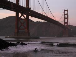 Surfers catch waves late in the day at Fort Point beneath the Golden Gate Bridge in San Francisco.