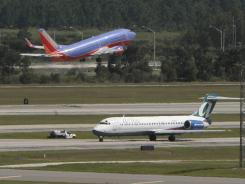 One jet takes off as another taxis at Orlando International Airport in 2010.