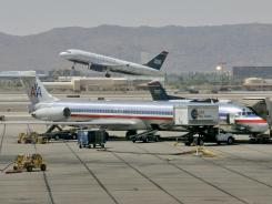 A US Airways jet takes-off as an American Airlines plane is prepped for take-off at Sky Harbor International in Phoenix in 2008.