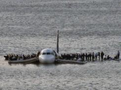 Passengers wait to be rescued on the wings of a US Airways Airbus 320 jetliner that safely landed in the Hudson River in New York, after a flock of birds knocked out both its engines. Agencies are working to reduce the dangerous collisions.