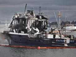 Fire officials stand near the smoldering hulk of the 91-ft. pleasure boat at Fisherman's Terminal that burned early Friday in Seattle.
