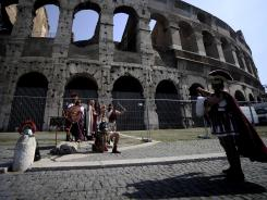 Men dressed as ancient Roman centurions take pictures with tourists by the Colosseum in Rome.