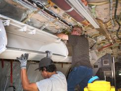 Workers in Tulsa install larger bins for carry-on luggage on a Boeing 737.