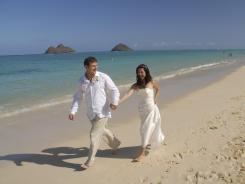 Sandra, right, and Sandy walk on the beach during their wedding at Lanikai Beach in Kailua, Hawaii.