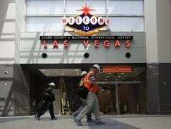 Construction workers walk along the main concourse of Terminal 3 at McCarran International in November.