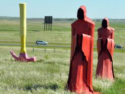 A pair of monks and an upside-down hammer stand firm in the breeze as cars whiz by Porter Sculpture Park, in Montrose, S.D.