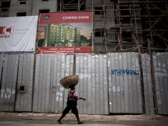 A street vendor walks in front of a building under construction for Best Western Hotel in Port-au-Prince, Haiti.