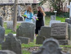 Kathleen O'Neil, 11, (left) and Arianna Bailey, 13, both of Wilmington, prowl in the cemetery surrounding Old Swedes Church for a school project at the historic site in Wilmington.