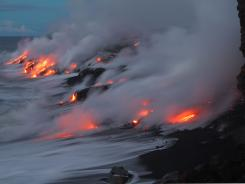 Lava from Kilauea Volcano in Hawaii Volcanoes National Park enters into the Pacific Ocean at dawn.