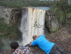 Visitors to Kaieteur National Park in Guyana get in position to take photos of the falls.