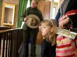 Amber Ehrlich, 4, of Chatham, Ill., and her mother Shelly listen to Lincoln Home National Historic Site park guide Crystal Cardoni describe the former president's family room in Springfield, Ill.