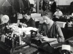 A woman sews neckties in the Cheney Brothers Silk Manufacturing Company in Manchester, Conn., circa 1915. State officials have funded a project to boost tourism by highlighting immigrants' stories.
