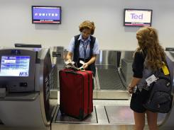 A United Airlines employee checks in a bag for a passenger at Miami International.