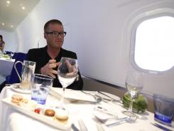 British celebrity chef Heston Blumenthal gestures as he talks in a mock up plane about his role in developing food for the London 2012 Olympics.