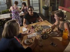 From left to right, Jessica Hall, Amy Hafez and Kiernan Waters share a pizza June 29 at Iggies in Baltimore.