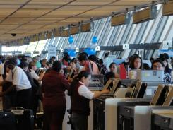 Airline passengers check-in for their flights in 2011 at Washington Dulles International Airport.