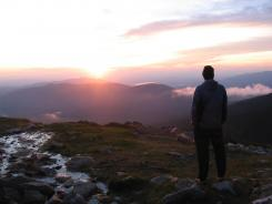 Paul Hugus, of Towson, Md. watches a sunset from outside the Lakes of the Clouds hut in the White Mountains on the Appalachian Trail.