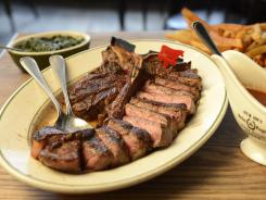 Porterhouse for two, with sides of creamed spinach and hand-cut fries. The steak is sliced and fanned out around the bone before it is served.