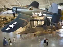 A WWII Vought F4U-1D Corsair is suspended over the Lockheed SR-71A Blackbird as tourists look at part of the Smithsonian Institute's Udvar-Hazy Air & Space Museum collection in Chantilly, Virginia.