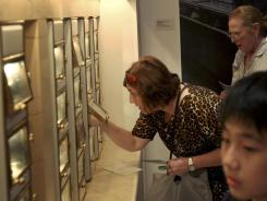 Visitors to the exhibit 'Lunch Hour NYC' play with an automat at the New York Public Library in New York.