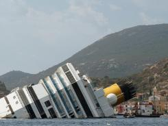 Salvage team members work at the rock embedded in the side of the Costa Concordia cruise ship near Giglio's harbor in July.