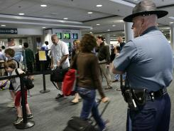 A Massachusetts state trooper keeps watch as travelers make their way through Logan International Airport in Boston.