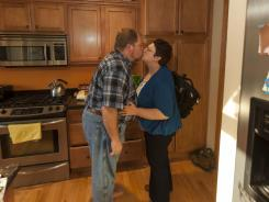 Keith and Stacey Symonds greet each other on Stacey's arrival at their Madison, Wis., home after her commute from Chicago.