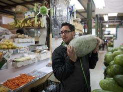 U.S. chef Christopher Kostow holds a watermelon as he visits Mercado San Juan Pugibet, the most gourmet market in Mexico City.