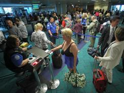 People wait in line at the security check point at Portland International Airport on July 3, 2012.