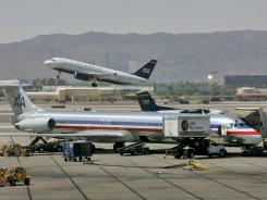In this June 23, 2008, file photo, a US Airways jet takes off as an American Airlines jet waits at the gate at Sky Harbor International Airport in Phoenix.