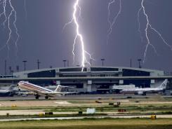 A bolt of lightning appears to strike near the terminals as a jet takes off from Dallas/Fort Worth in 2006.