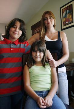 "Doris Chiquito, right, and her children Jonathan, 11, left, and Ariana Gonzalez, 8, at their home in Coral Gables, Fla. Chiquito, 30, who was born in the U.S. to Ecuadorian parents and is fluent in English, says she enrolled her son and daughter in bilingual classes so they would also speak Spanish and not ""feel ashamed of being Hispanic."""