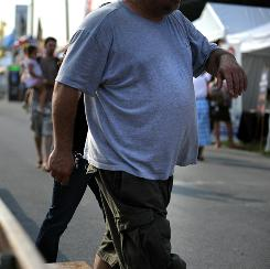 An overweight man walks at the Montgomery County Agricultural Fair in Gaithersburg, Md. Obesity adds more than $2,800 to a person's annual medical bills, a study finds.