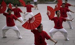 "Women practice tai chi in Beijing, China, June 27. Tai chi, sometimes known as ""shadow boxing,"" is a form of martial arts which combines slow graceful movements with meditation."