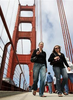 "Pedestrians walk across the Golden Gate Bridge in San Francisco. The ""city by the bay"" was ranked No. 1 in major metro areas as a college destination."