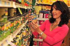 Bonnie Taub-Dix reads the nutrition information on canned food at a Foodtown in New York.