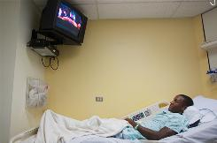 Heyward Demison watches the Oregon Ducks football game in his room at the pediatric unit at Legacy Emmanuel Hospital on Sept. 11 after he suffered a serious heart attack while playing a football game for Central Catholic High School in Oregon. Demison was diagnosed with a heart defect requiring surgery.