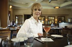 Breast cancer survivor Brenda Coffee relaxes with a cosmopolitan at the bar of Piatti at the Quarry in San Antonio, Texas.